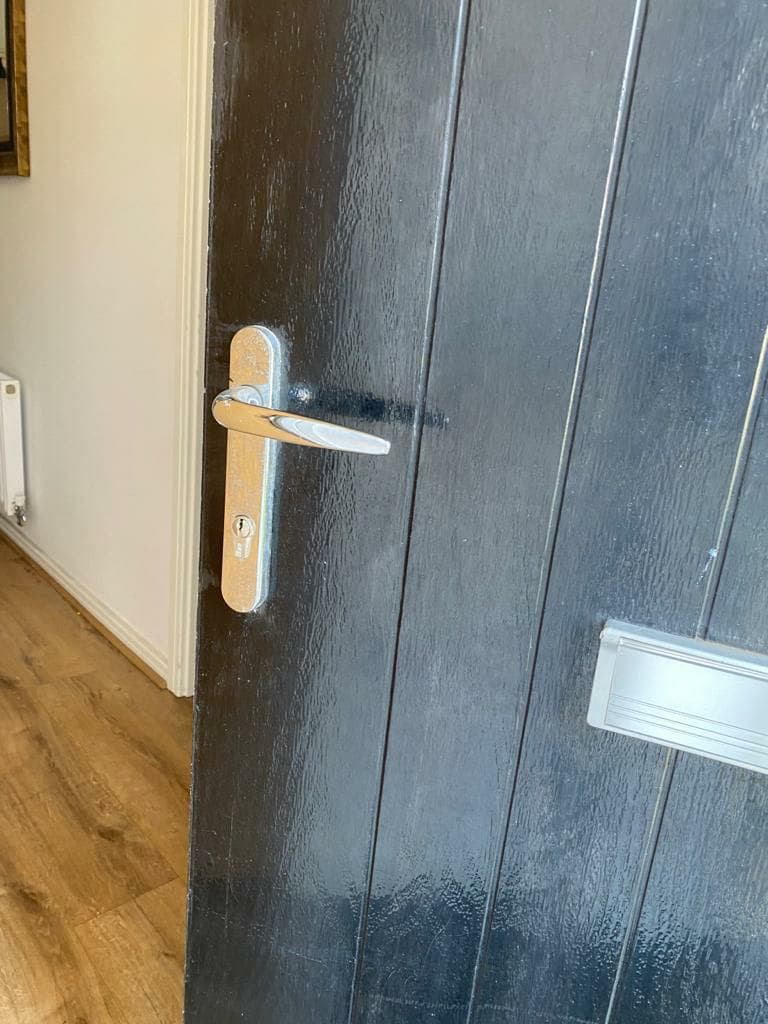 A black door with a new handle.